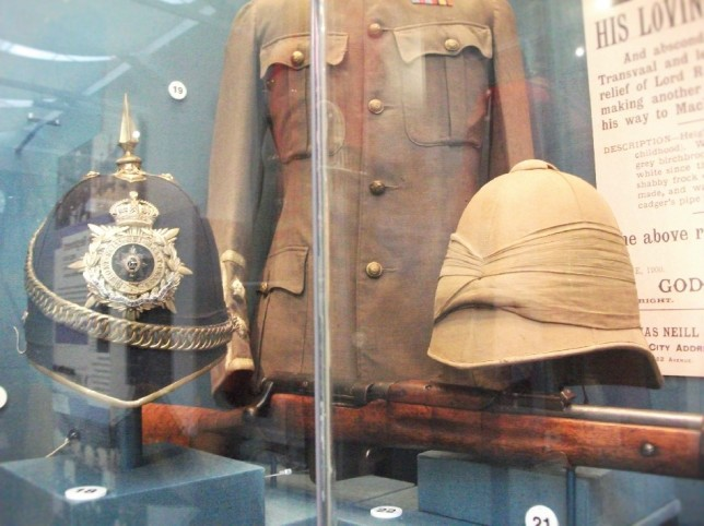 Full dress helmet and service helmet with khaki uniform behind.